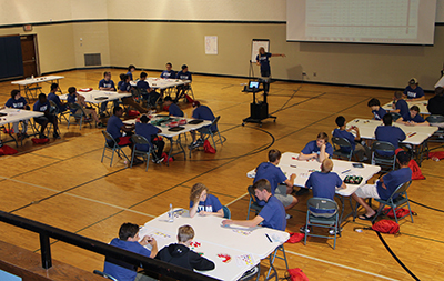 STEM camp students working on a Lego manufacturing simulation