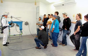 A photo of event attendees listening to the waterborne spray paint demonstration inside Dunwoody's spray paint booth