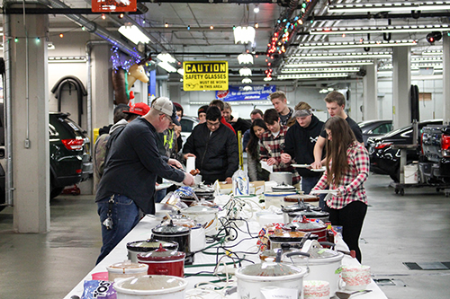 Dunwoody Automotive students loading up their lunch plates at the annual holiday potluck event in the Warren building