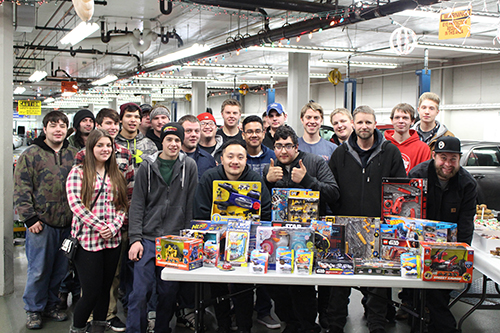 Dunwoody Automotive students standing next to toys being donated to Toys for Tots
