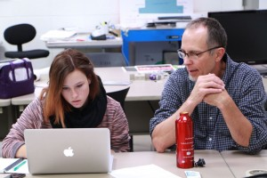 Graphic Design Instructor Tom Herold works with a student during class.