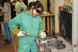 Photo of girl welding in welding lab.
