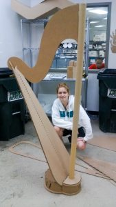 Karen West with the full-sized concert harp made from corrugated cardboard.