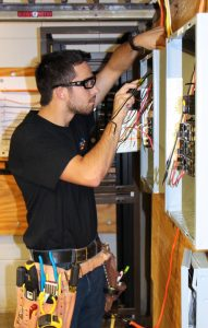 Dunwoody Electrical Construction & Maintenance student practices residential wiring inside Dunwoody's onsite house