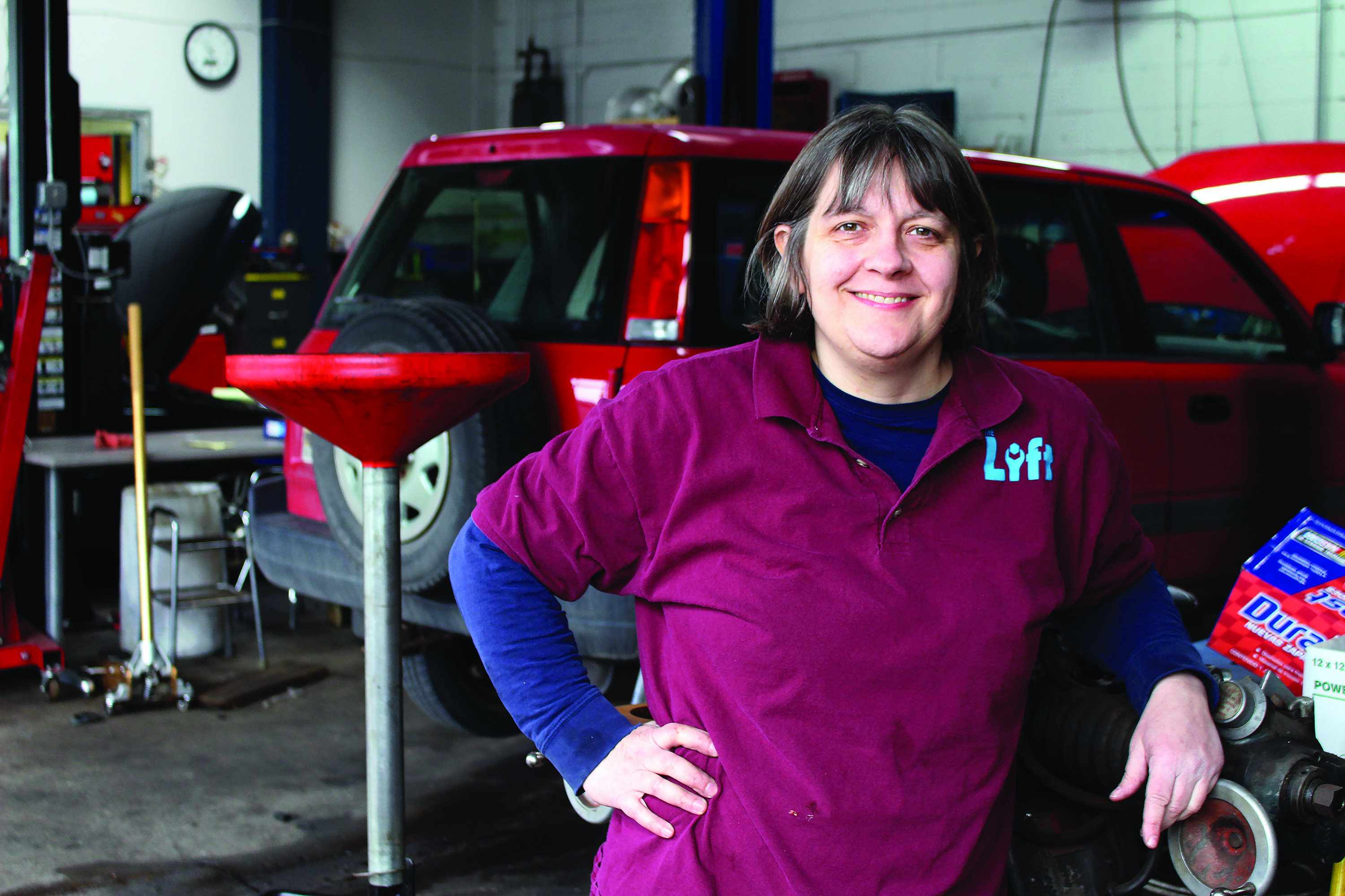 Cathy Heying, Dunwoody Alumni and founder of The Lift Garage, stands next to a car she is repairing. Headshot.