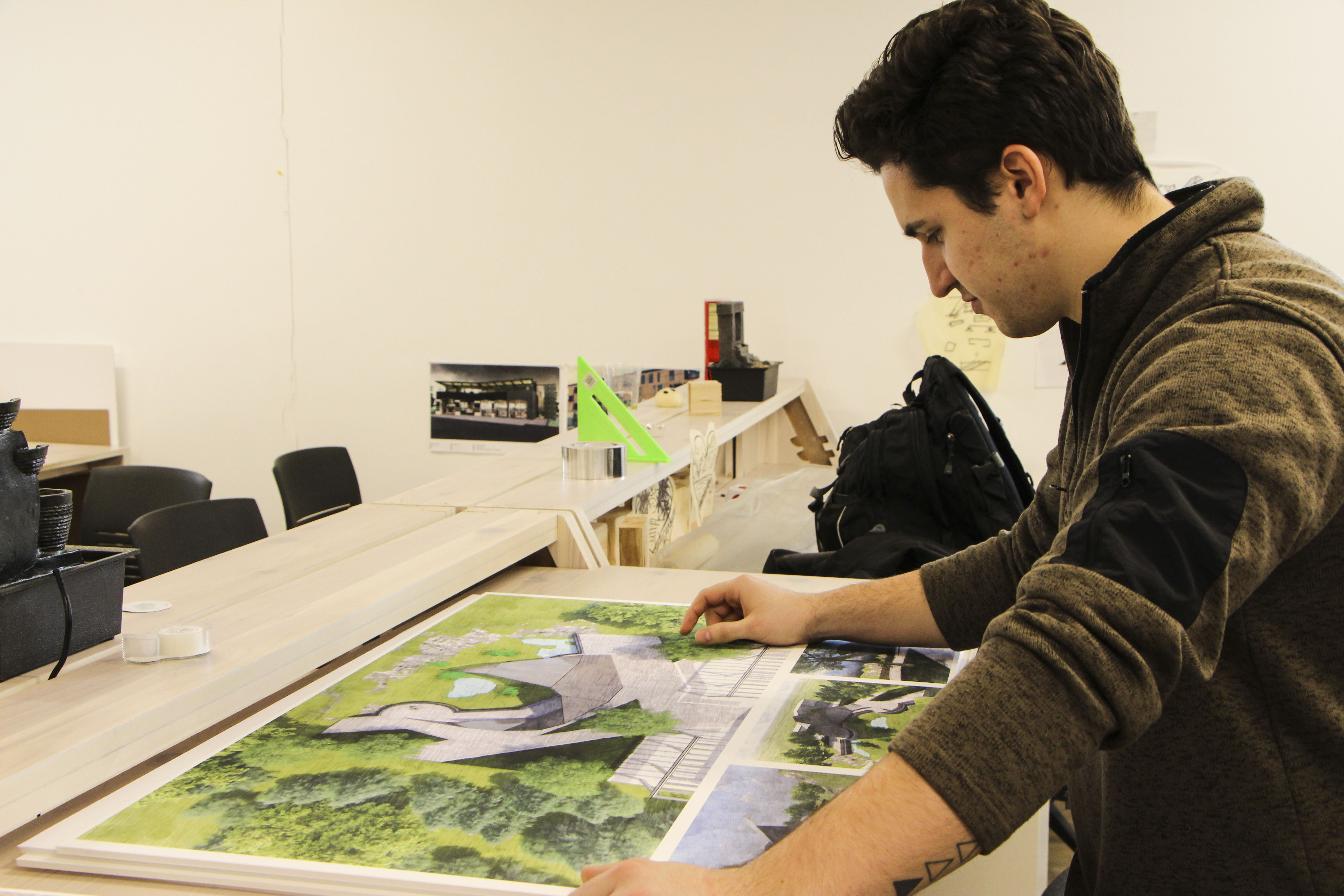 Student Austin Rastall with his renderings for the Como Park project