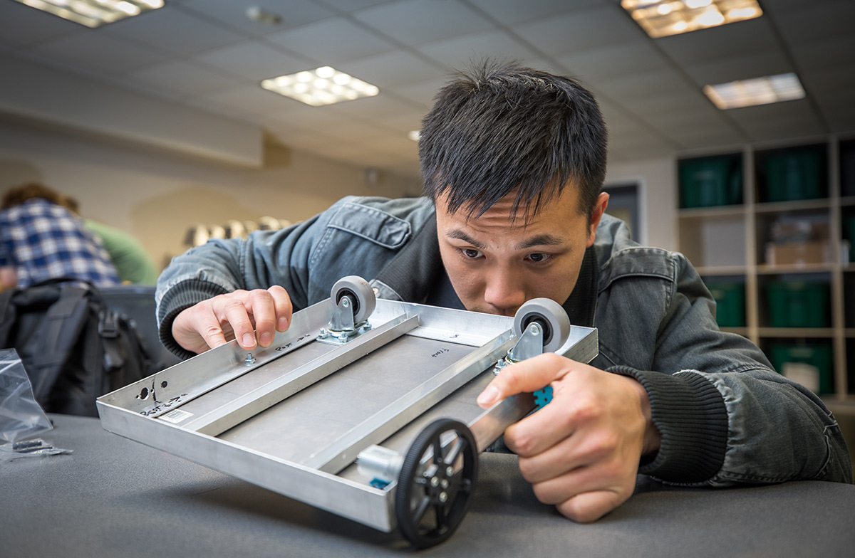 Photo of a first-year engineering student inspecting the bottom housing for a robot