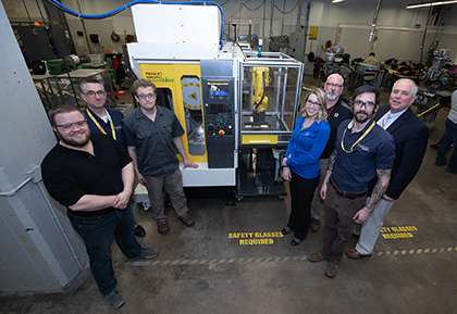 Dunwoody students, faculty, and administrators standing in front of the Fanuc MTEC alongside representatives from Graco