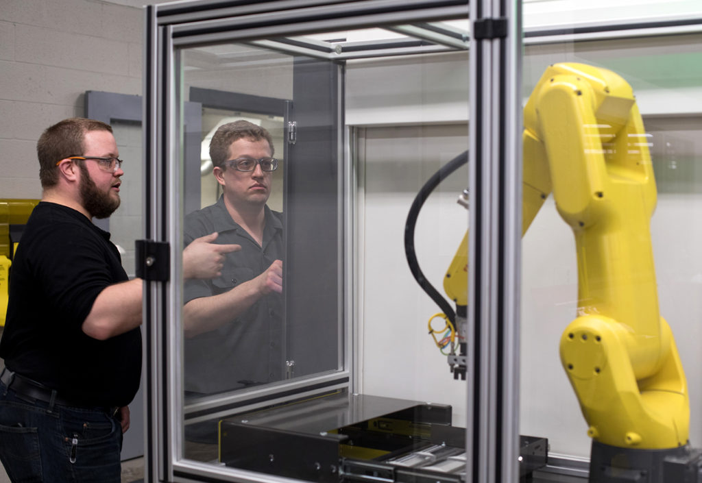 Two students looking at the robotic arm that's part of the Fanuc MTEC