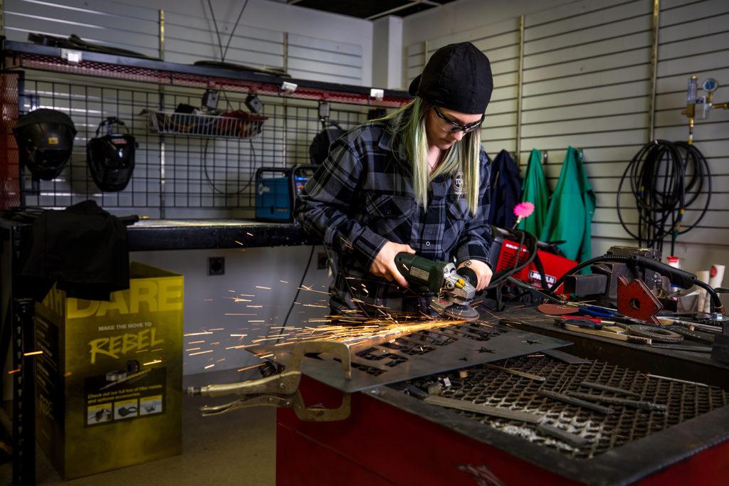 Alex Mars grinds a sign in her Lakeville shop.
