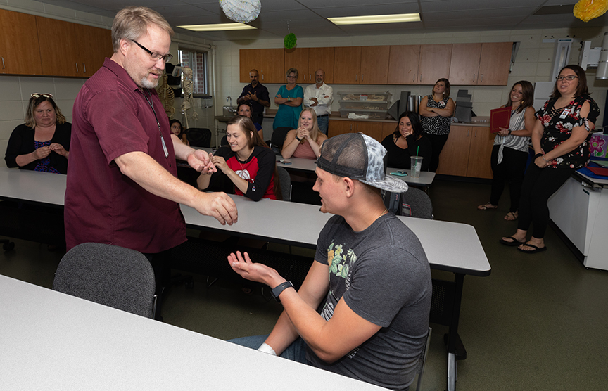 David Blake, Program Manager for Radiologic Technology, hands Brayden Snow his pin during the Rad Tech Pinning Ceremony.
