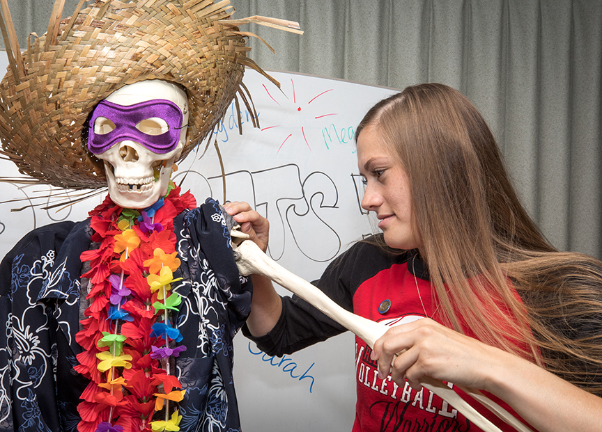 Amber Skelton fixes the arm of Mr. Bones during a class celebration.