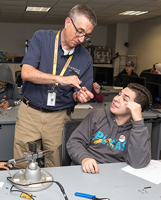 E.J. Daigle, left, Dean of Robotics & Manufacturing, answers a question Mark Velez had about connecting wires while building a flashlight in a lab.