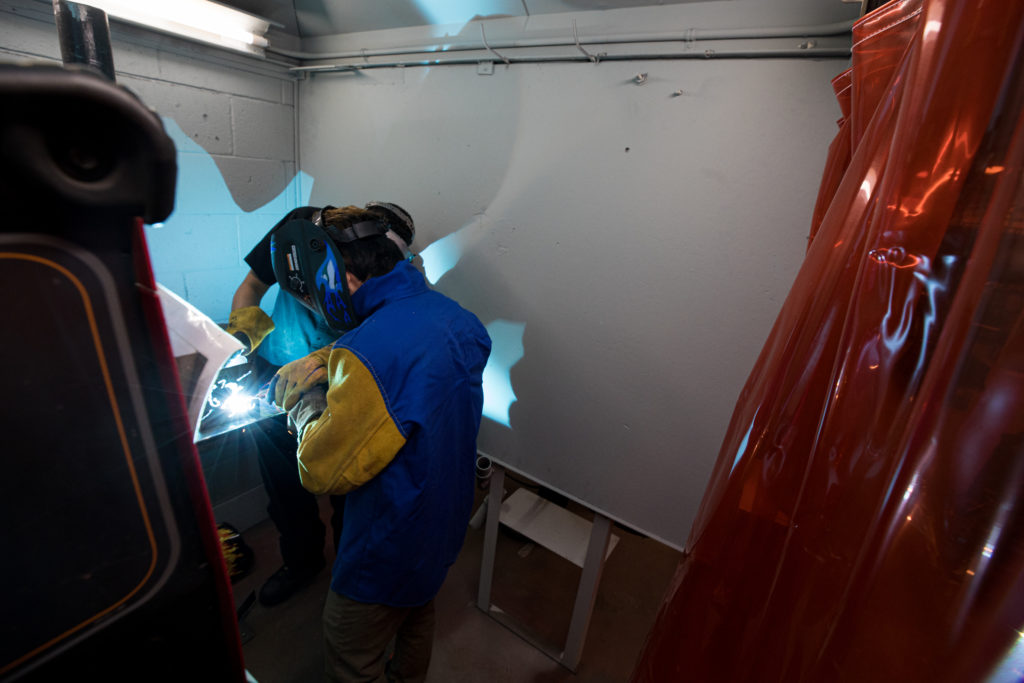 Zhiwei Blaubach in the welding booth during a YCAP session.