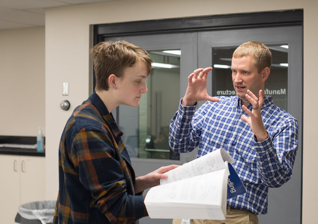 Andrew Hoitink explains a classroom exercise to a student