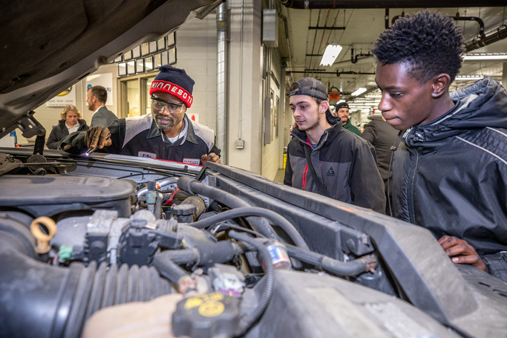 Students looking over engine