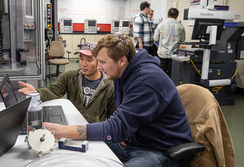 Mechanical Engineering students Tommy Dao, left, works with fellow student Dan Hurd in the Metrology lab on their senior capstone project.