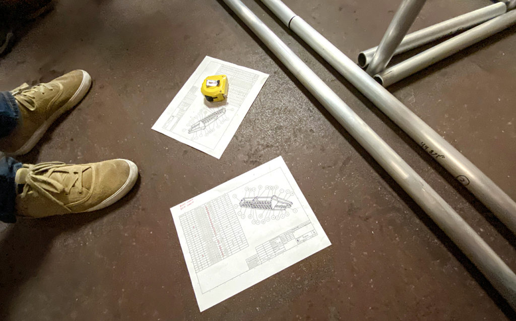 Plans for the SuperMileage build sits on the floor in the Welding Shop for reference.
