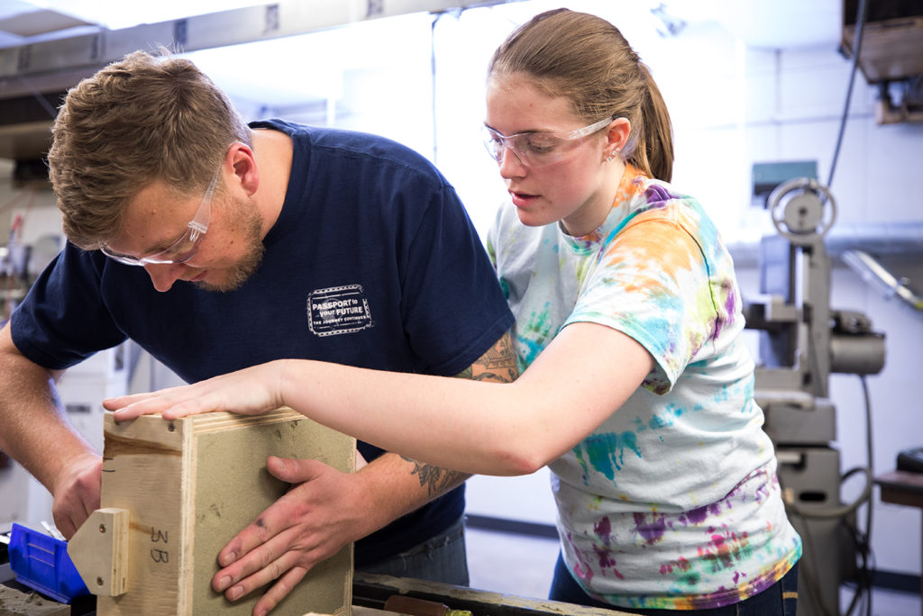 Mechanical Engineering students Dan Hurd, left, and Angela Freeland, right, sandcast a mold to make aluminum wrenches in the Foundry.