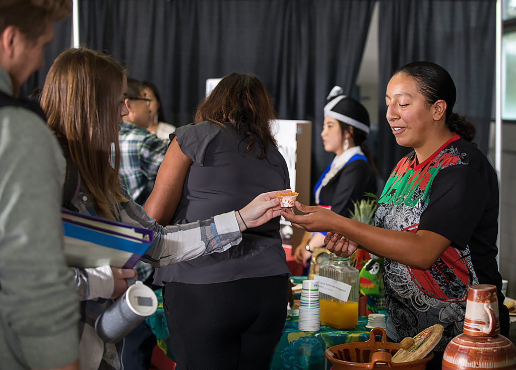 Liz Rivas,right, shares food she made with other students during the Festival of Cultures.