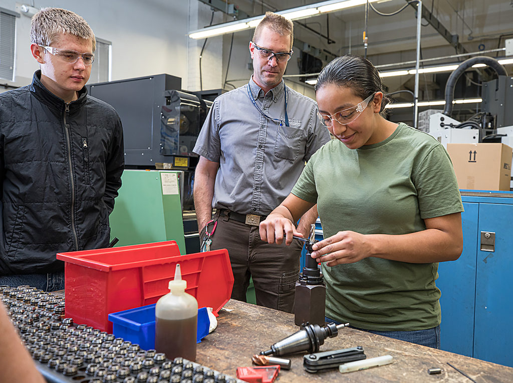 Liz Rivas, right, with her instructor and classmates learn about CNC machines during lab.