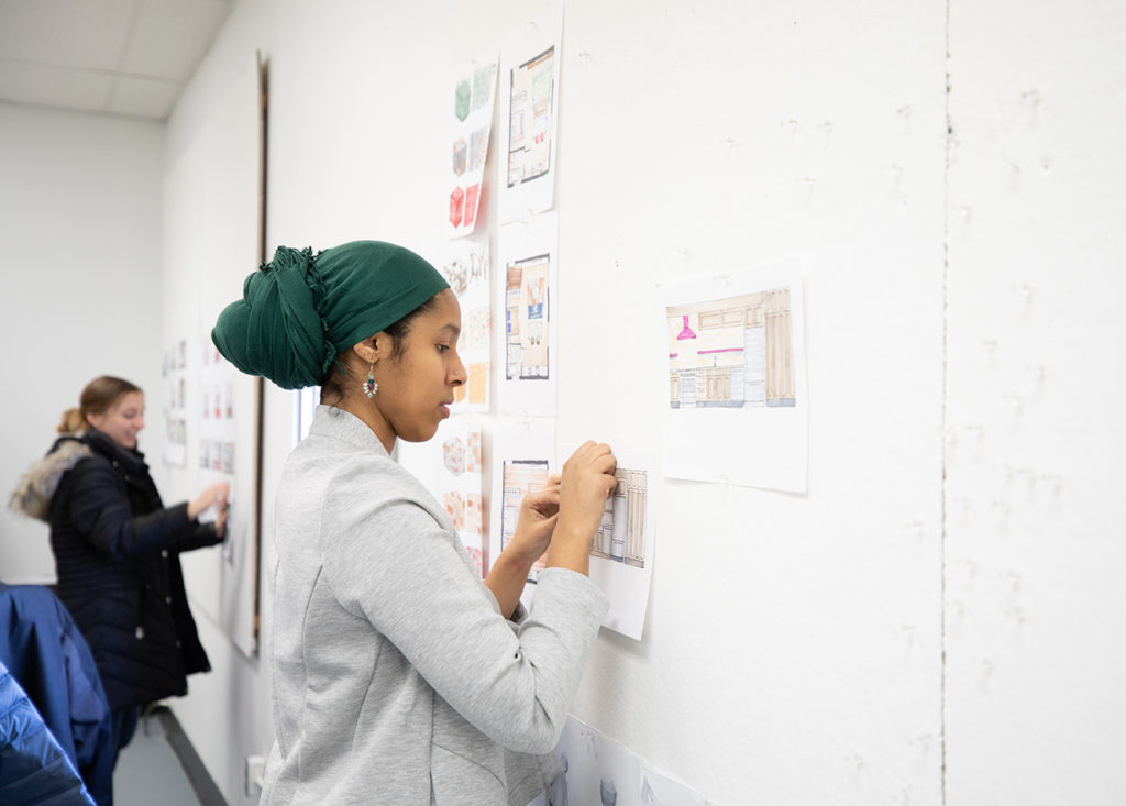 Interior Design student Sumeya Mohamed pins her work to the board during class.