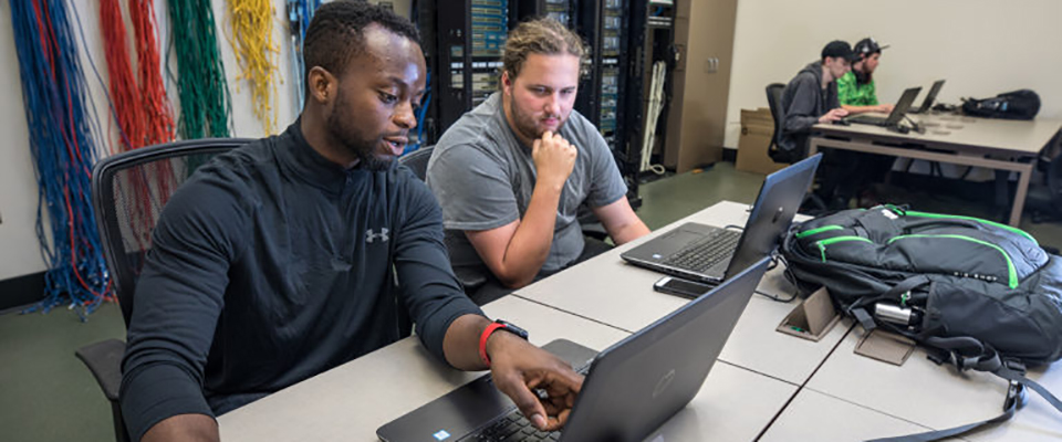 Software Engineering students Ben Oluwalowo, left, and and Brendan Vandevoorde, right, work together on a software engineering project which will identify areas of software improvement in high-speed car chases.