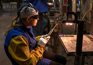 A female welding student welding on day two of classes