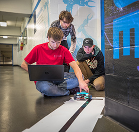 Three first-year engineering students testing a robot they built