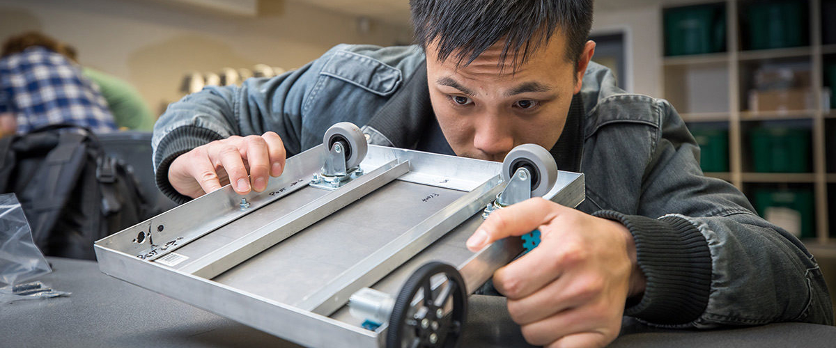 An engineering student inspects the bottom frame of an autonomous robot