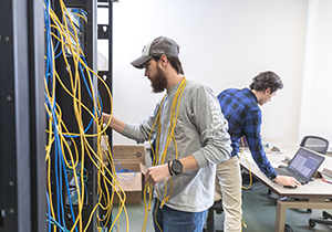 Adam Huber, left and Ryan Thelan work on a complete simulation of a global network, with multiple different regions (Customer Sites) and Internet Service Providers during his Routing and Switching II class