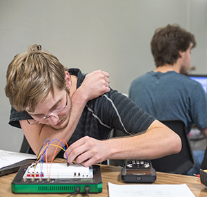 An electrical engineering student working on a breadboard