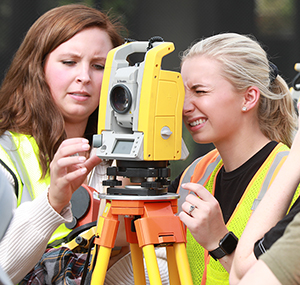 A photo of two students using surveying equipment