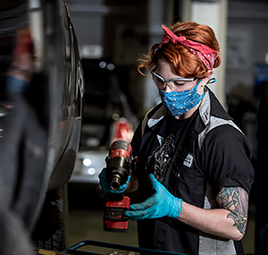 A student in Automotive class wearing a face mask and gloves while working on a vehicle